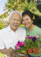 caregiver and old man holding flower pots