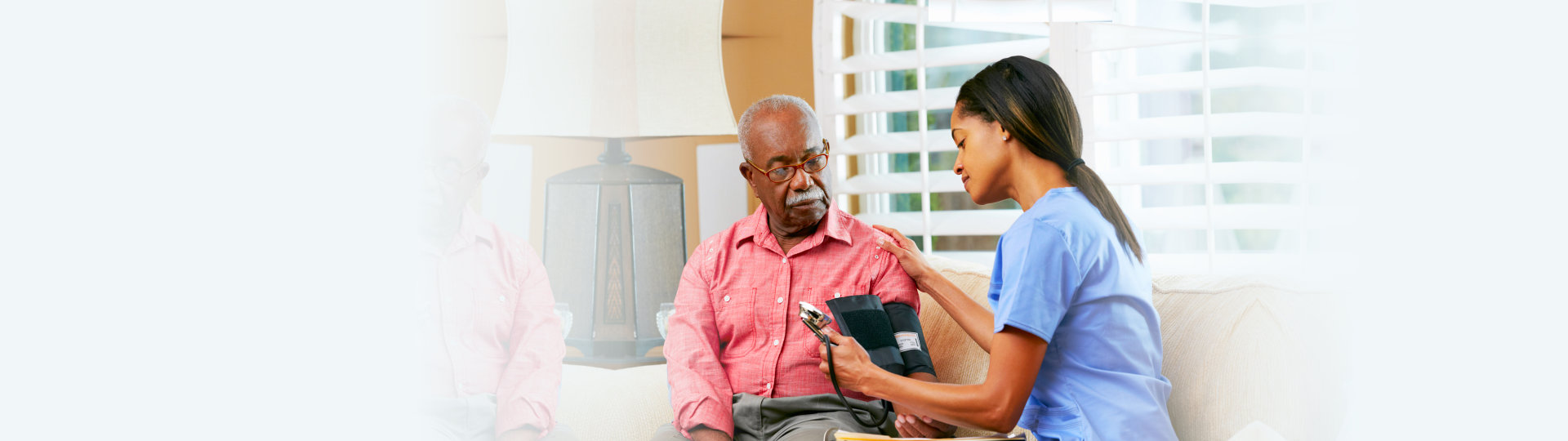 caregiver checking blood pressure of old man